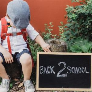 Child holding back to school sign